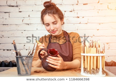 Young woman decorating pottery in workshop Stock photo © Elnur