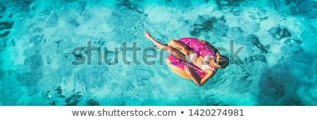 women in bikini swimsuit swim in inflatable rings stock photo © robuart