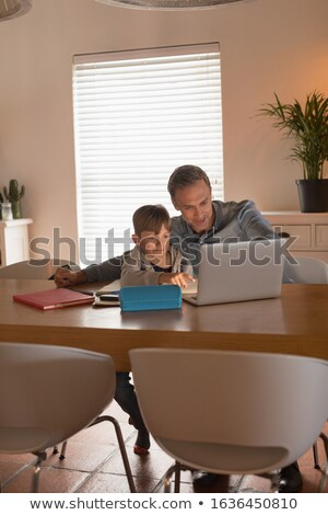 Front view of caring father helping his son with his homework while using laptop at home Stock photo © wavebreak_media