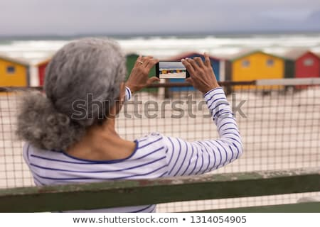 Rear view of senior woman clicking photo with mobile phone while sitting on promenade bench at beach Stock photo © wavebreak_media
