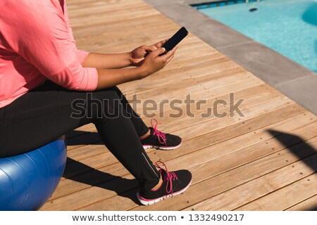 Low section of middle-aged African American woman using mobile phone while sitting on exercise ball  Stock photo © wavebreak_media