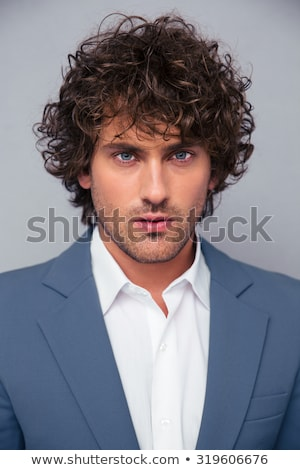 Handsome confident young curly haired businessman Stock photo © deandrobot