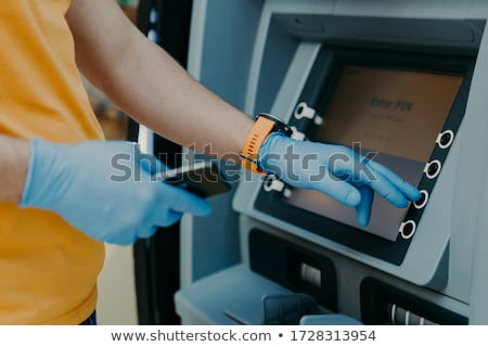 Cropped shot of man wears protective rubber gloves, uses ATM machie to withdraw money, prevents from Stock photo © vkstudio