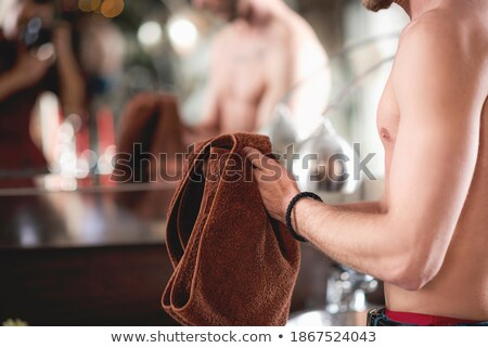 Wet muscular man wiping himself with a towel Stock photo © stockyimages