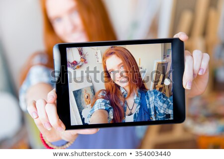 Positive smiling  woman making selfie using tablet in artist workshop Stock photo © deandrobot