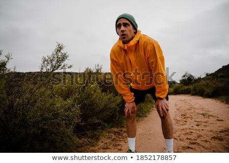 Young handsome athlete standing in the rain Stock photo © konradbak