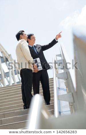 businessman holding newspaper and pointing at something outdoor stock photo © deandrobot
