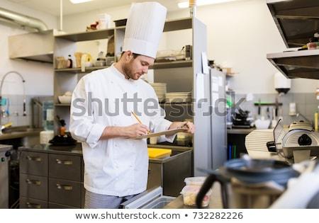 Kucharz patrząc celu listy handlowych kuchnia Zdjęcia stock © wavebreak_media