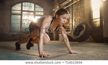 Athletic girl does exercise in gym Stock photo © bezikus