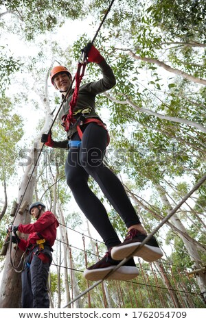 Stock photo: Young woman wearing safety helmet holding zip line cable in the forest