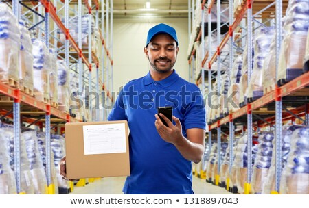 Stock photo: Worker in logistics warehouse on the phone
