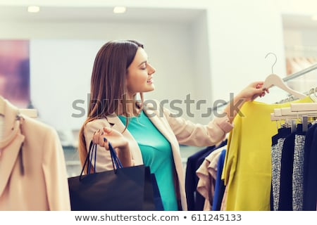 sale, fashion, consumerism and people concept - happy young woman with shopping bags choosing clothe Stock photo © galitskaya