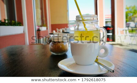 Brown cane sugar in glass jar and wooden spoon closeup image.  Stock photo © marylooo