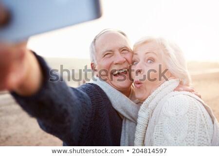 happy couple taking selfie on beach in autumn stock photo © dolgachov