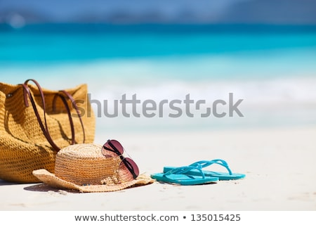 straw hat, flip flops and sunglasses on beach sand Stock photo © dolgachov