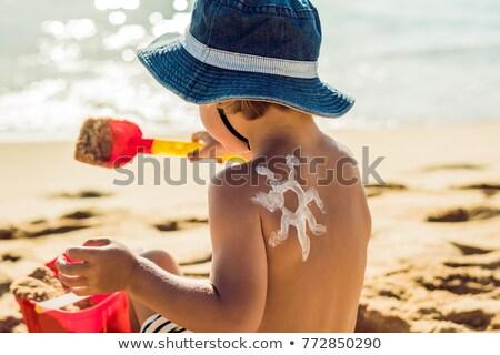 Boy applying sunscreen Stock photo © elenaphoto