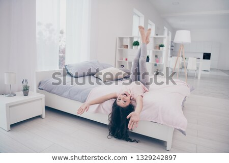 A woman lying down the length of her bed as she smiles and interacts with her smartphone. Stock photo © wavebreak_media