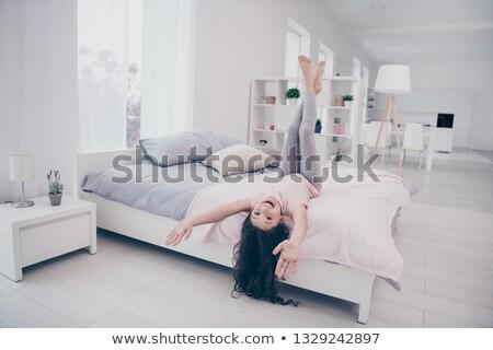 женщину длина кровать улыбается смартфон Сток-фото © wavebreak_media