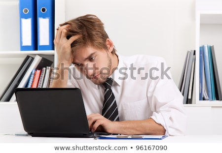 Frustrated Businessman Sitting At Desk In Office Using Laptop Stock photo © Rugdal