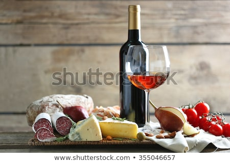 Red wine bottle, cheese and tomato still life  Stock photo © natika