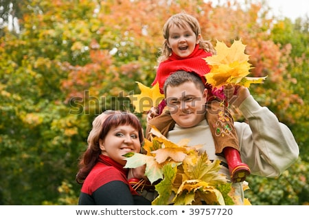 Stock photo: married couple and little girl collect maple leafs in park in au