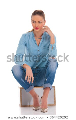 model in denim pose seated in studio background with hand on kne Stock photo © feedough