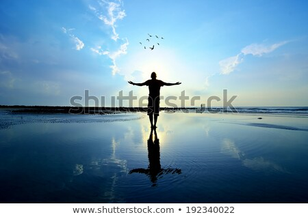 Silhouette of a man raising his hands or open arms on the beach  Stock photo © dashapetrenko
