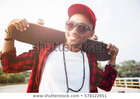 Young dark skinned man wearing sunglasses holding skateboard Stock photo © deandrobot