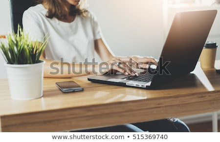 tech hipster working at wooden desk on laptop stock photo © paulinkl