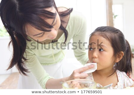 Mother wiping daughter's mouth Stock photo © IS2