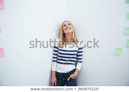 business woman with hands in pockets looks up stock photo © feedough