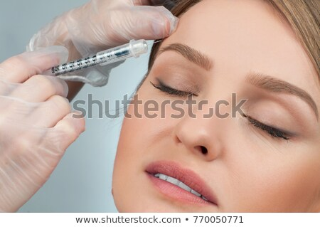 Woman is getting injection over eyebrow. Anti-aging treatment and face lift. Cosmetic Treatment and  Stock photo © flisakd