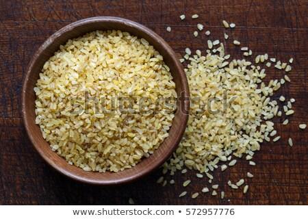 Dry bulgur wheat in wooden bowl isolated Spilled bulgur Stock photo © Virgin