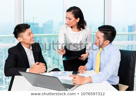 Asian banker counseling man in office Stock photo © Kzenon