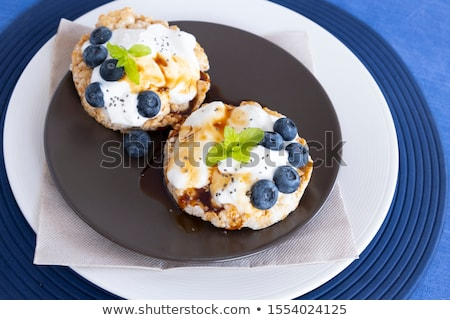 healthy organic rice cakes with ricotta and fresh blueberries on wooden board and glass of milk on l stock photo © denismart