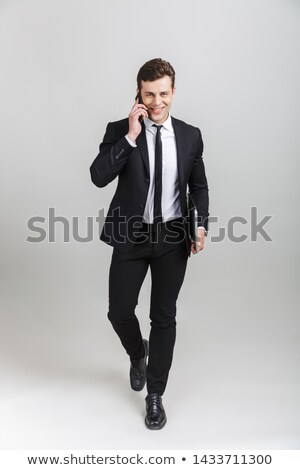 image of joyful businessman 30s in suit smiling while holding la stock photo © deandrobot