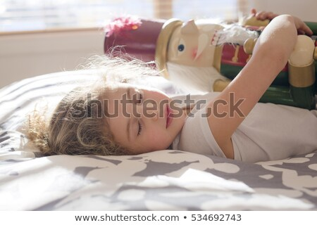 beauty child who holding a nutcracker in bed stock photo © lopolo