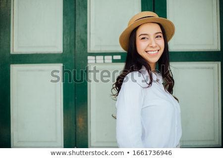 Portrait of a cheerful young asian woman in straw hat Stock photo © deandrobot