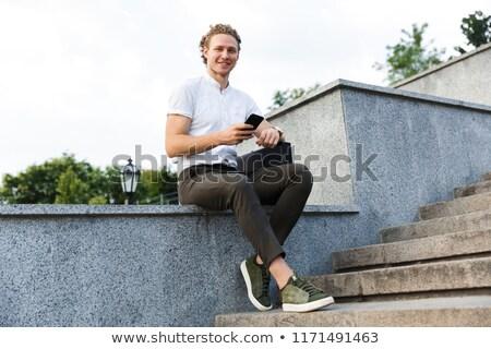 Uśmiechnięty człowiek biznesu teczki smartphone Zdjęcia stock © deandrobot
