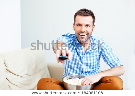 handsome man sitting on sofa at home and changing tv channels w stock photo © deandrobot