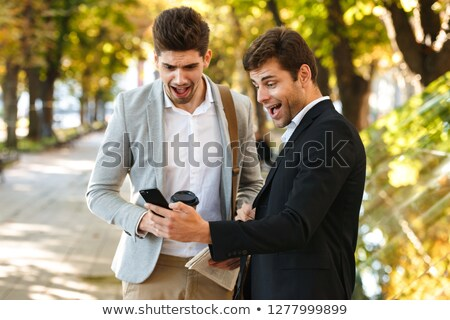 Photo of joyous businessmen in suits using smartphone while walk Stock photo © deandrobot