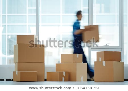 Young man employee with boxes in the office  Stock photo © Elnur