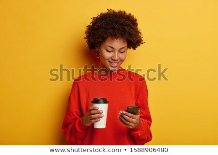 Indoor shot of cheerful millennial woman with Afro hairstyle, lies on stomach in comfortable bed, ch Stock photo © vkstudio