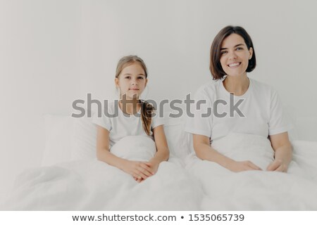 Horizontal shot of relaxed mom and daughter sit in bed under white blanket, look gladfully into came Stock photo © vkstudio
