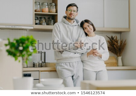 Shot of relaxed family couple stand in kitchen, drink takeaway coffee, wear casual outfit, pose in k Stock photo © vkstudio