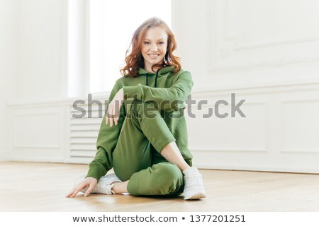 Positive redhead fitness girl feels relaxed, wears tracksuit, sportshoes, has rest after yoga traini Stock photo © vkstudio