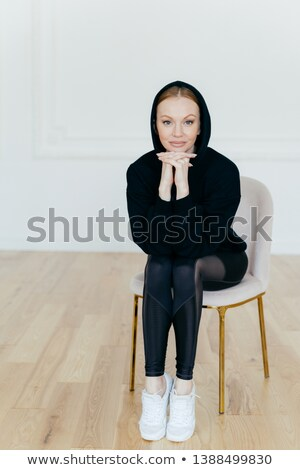 Vertical shot of good looking woman with make up, keeps hands under chin, wears hoody, leggings and  Stock photo © vkstudio