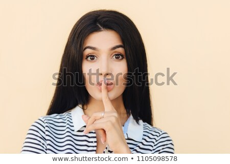 Secret female makes hush sign, gossips with best friend, keeps index finger on lips, has long dark h Stock photo © vkstudio