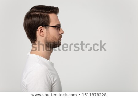 Close up shot of pleasant looking bearded male with thoughtful expression, keeps finger on chin, loo Stock photo © vkstudio