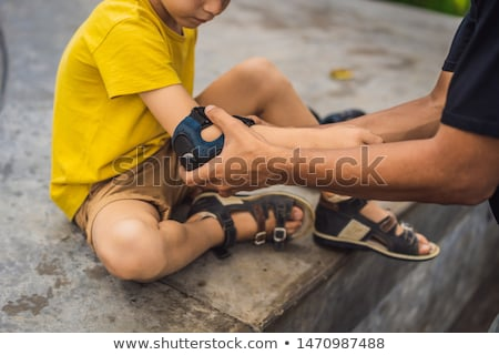 Trainer helps the boy to wear knee pads and armbands before training skate board BANNER, LONG FORMAT Stock photo © galitskaya